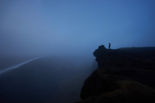 Homeschool parent standing on cliff overlooking blue fog abyss