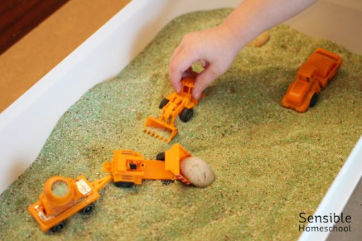 Kid playing with trucks in mini indoor sandbox with green sand