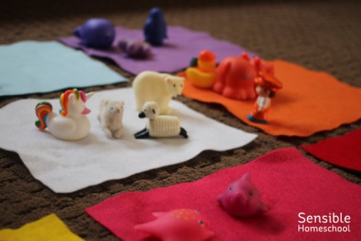 toddler color matching game with colored felt rectangles and colored plastic toy animals