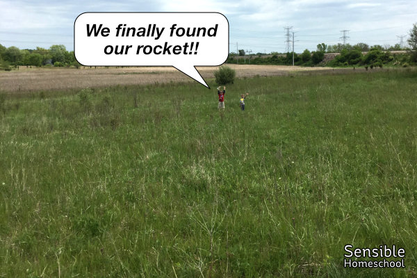 """boys far away in field with text """"We finally found our rocket!!"""""""