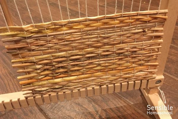 Straw mat being woven in kid's weaving loom