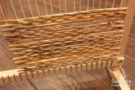Straw mat being woven in kid's weaving loom