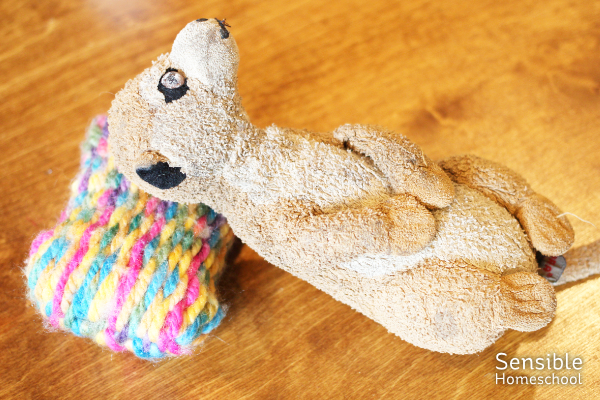 Stuffed animal meerkat laying on small, homemade, woven rainbow-colored pillow