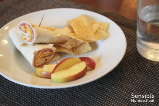 ham and cheese wrap with tortilla chips and apple slices on white plate