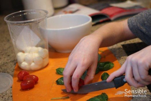 Homeschool boy preparing salad from kid's cookbook.