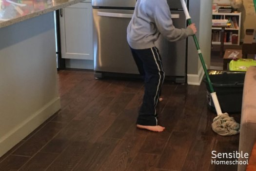 Homeschool fifth-grader mopping kitchen floor