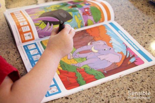 Homeschool preschooler working on Hidden Pictures book at kitchen island
