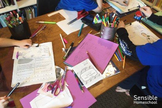 Messy homeschool table with three homeschool kids working