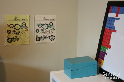 homeschool room All About Spelling magnet tiles, phonogram card box and progress charts on wall