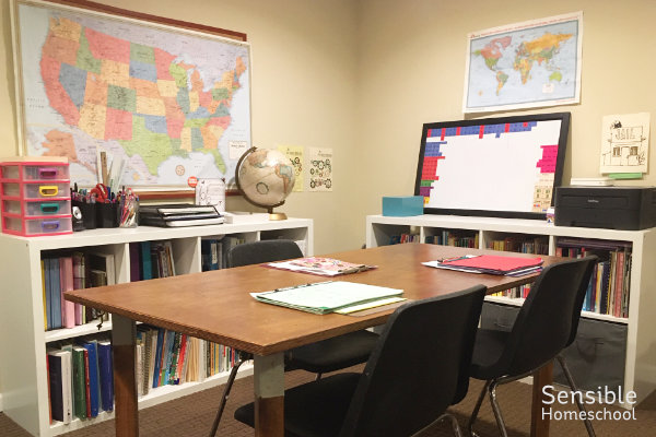 Homeschool study room corner with table, maps and curriculum shelves