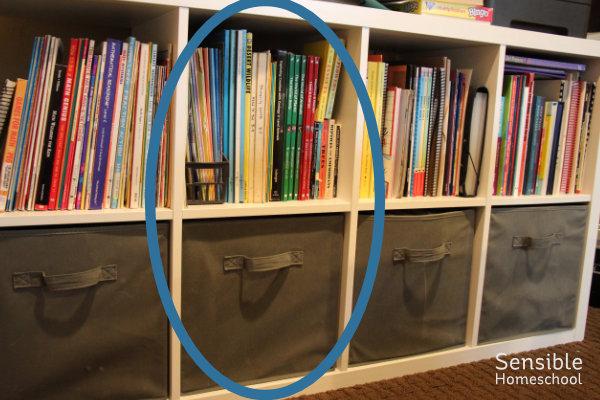 Homeschool curriculum shelf with science shelf and bin circled