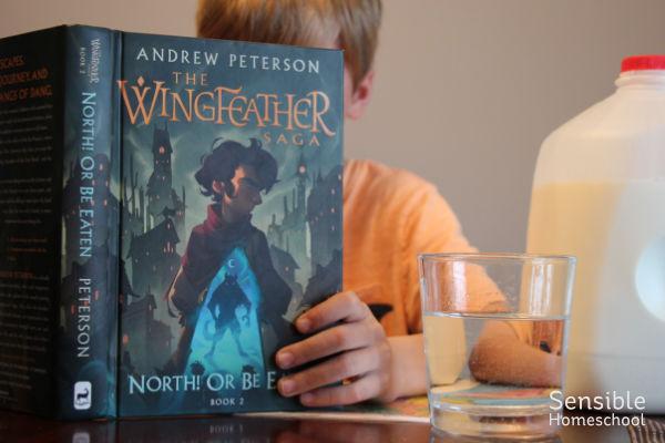 Homeschooler reading while eating breakfast