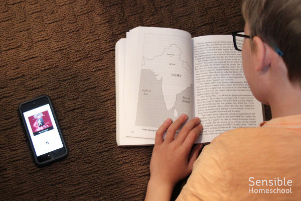 homeschool student listening to story of the world history audiobook and reading history book