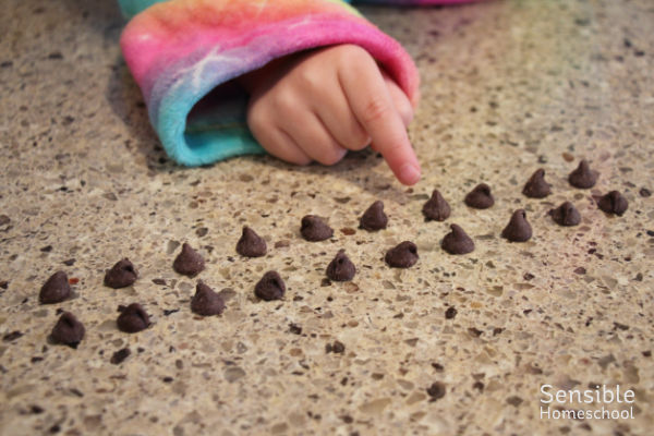 Preschooler counting chocolate chips by twos