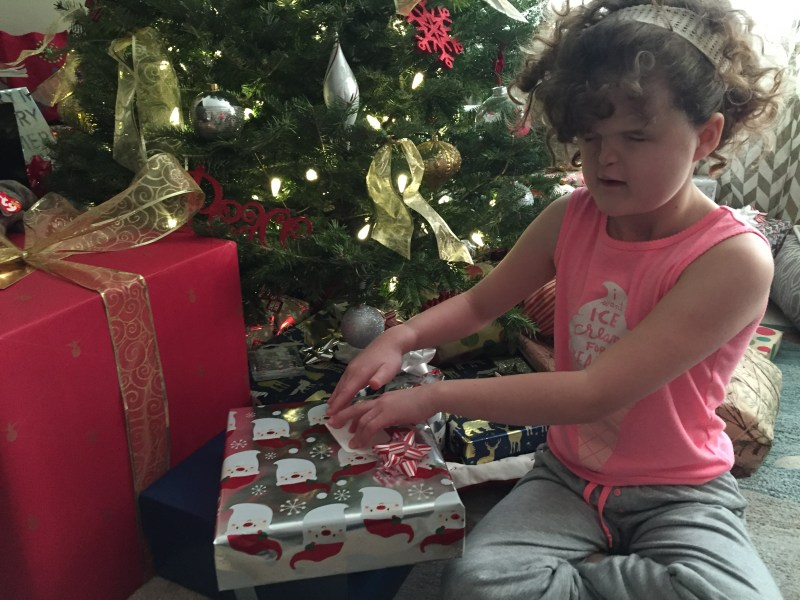 girl with presents in front of tree