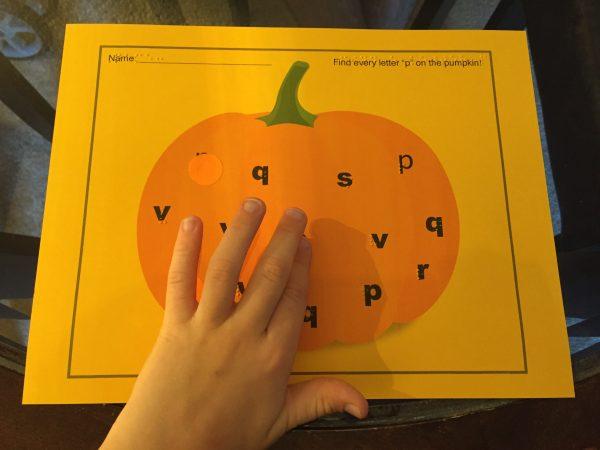 Madilyn reading braille letters on pumpkin worksheet