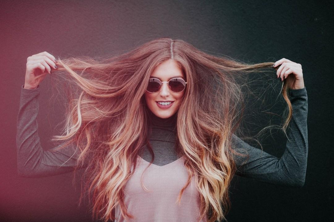 Kvinne med flott hår ser mot kamera, og drar håret til ut i luften