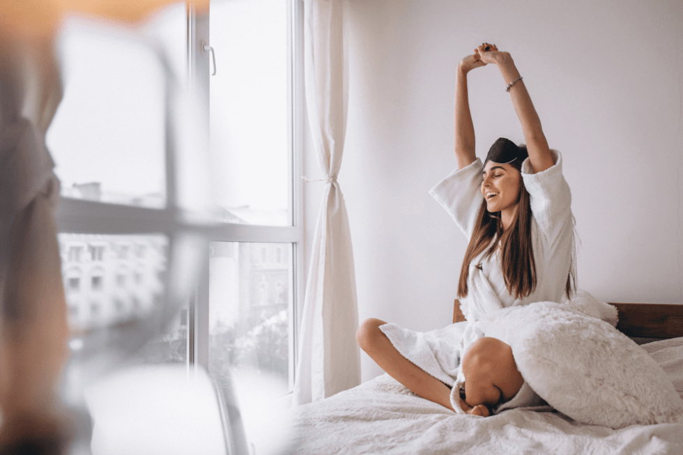 Young woman wakes up in the morning feeling happy