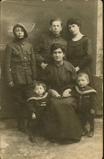 My father is the little boy on the left. His brother, Chaim, on the right. The woman holding their hands is my great grandmother. Miriam, my grandmother is to the rear. This photo was taken in Poland. The men in uniform are probably relatives, but I don't know who they are.