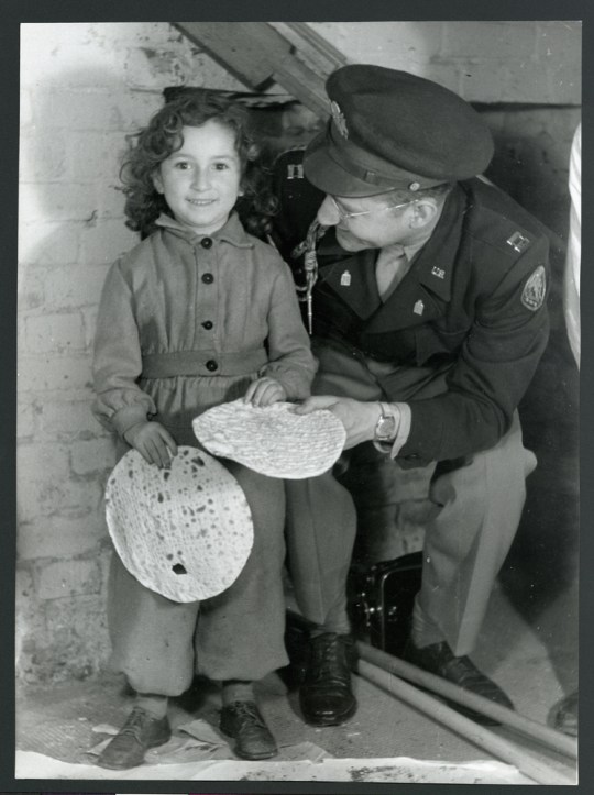 A young Jewish girl in the JDC-supported Berlin-Mariendorf DP Camp shares matzahs with Captain J. Robbins, Jewish Chaplain for Berlin. Berlin, c 1946.
