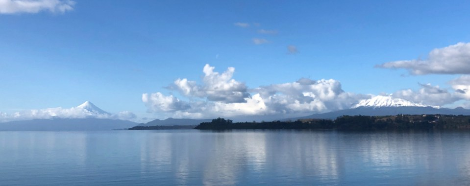 Photo of lake and two volcanoes with blue skies.