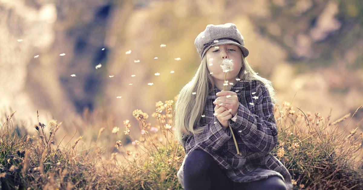 Bambina che soffia su un fiore di tarassaco