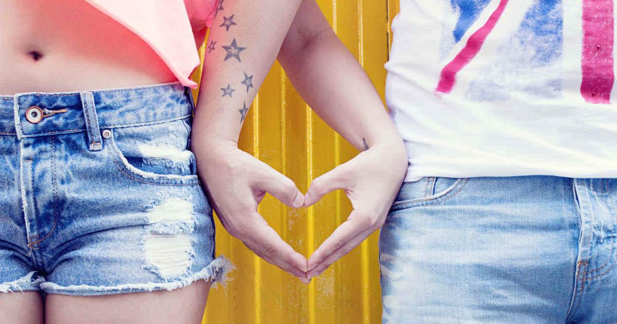 Un ragazzo e una ragazza con le mani a forma di cuore