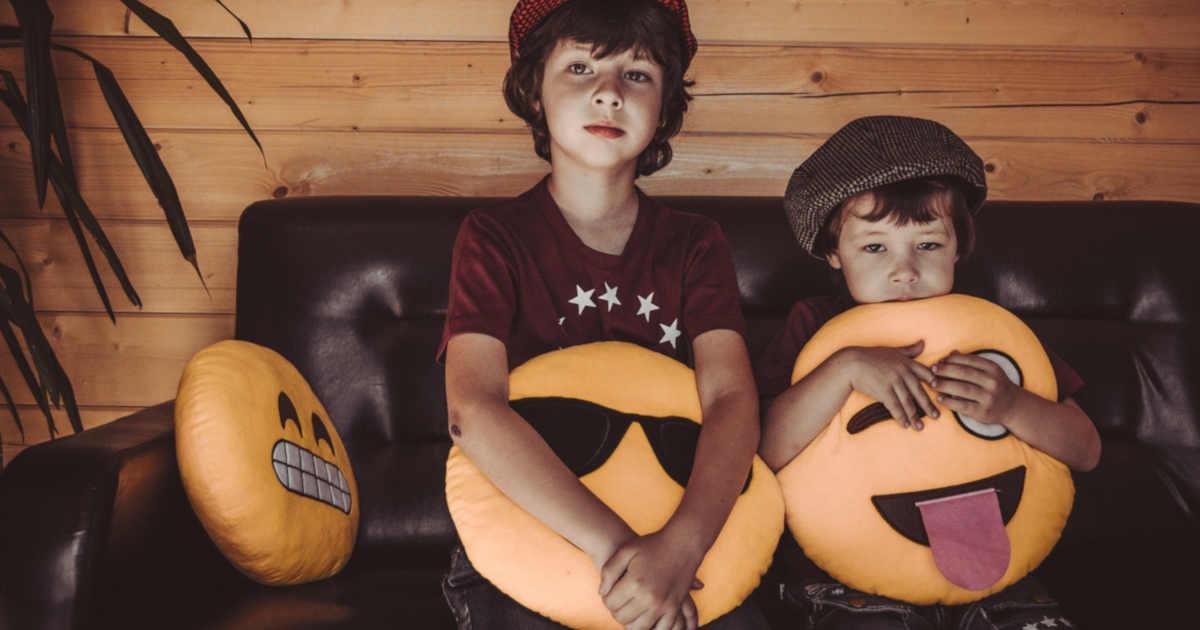 Bambini con in braccio dei cuscino a forma di emoji.