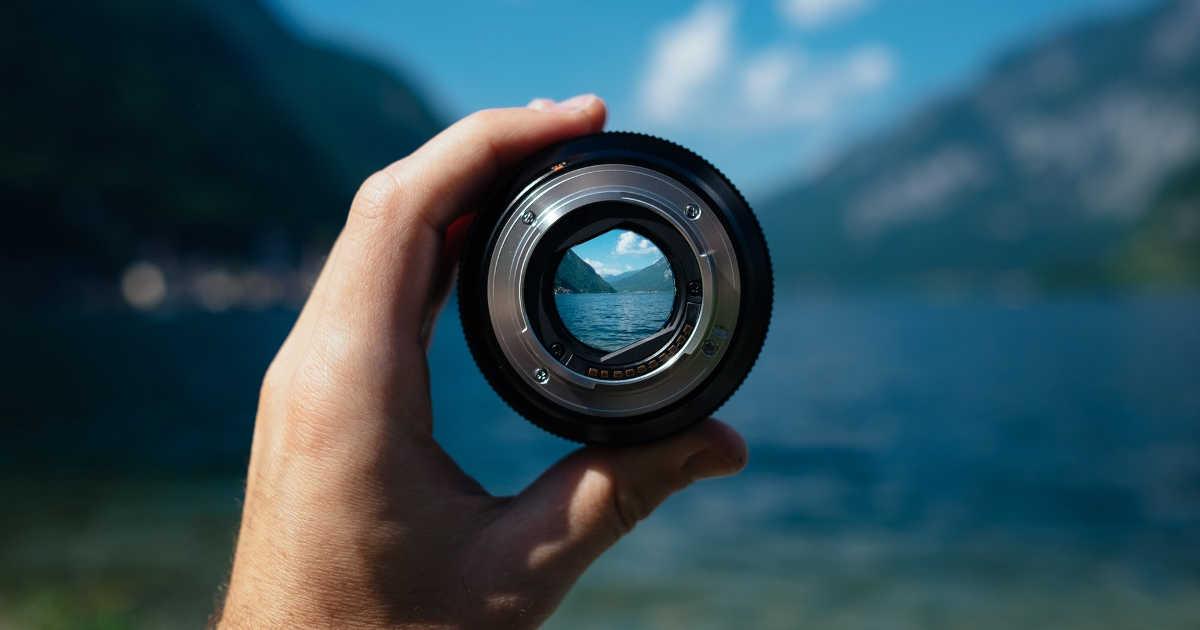 Una mano che tiene un obiettivo fotografico per mettere a fuoco l'orizzonte