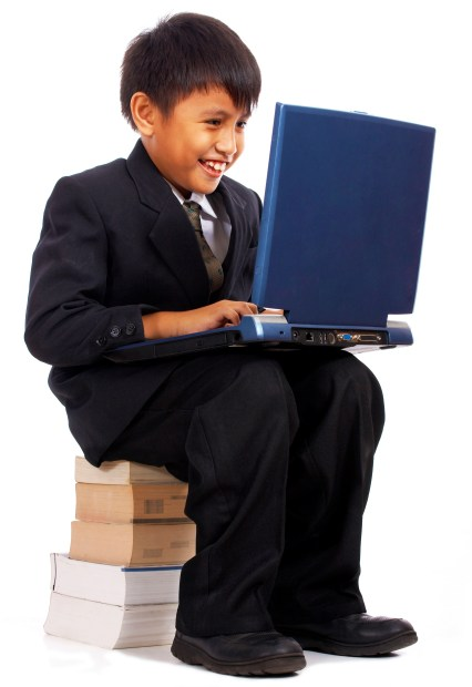 Boy On His Computer Studying For School And Sitting On A Pile Of Books