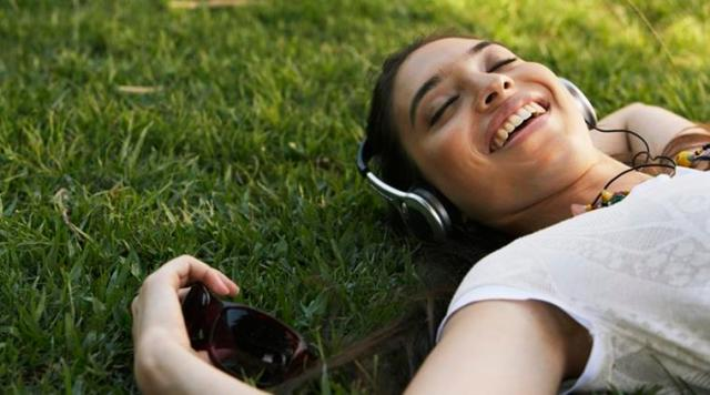 Young woman lying on grass, wearing headphones, smiling