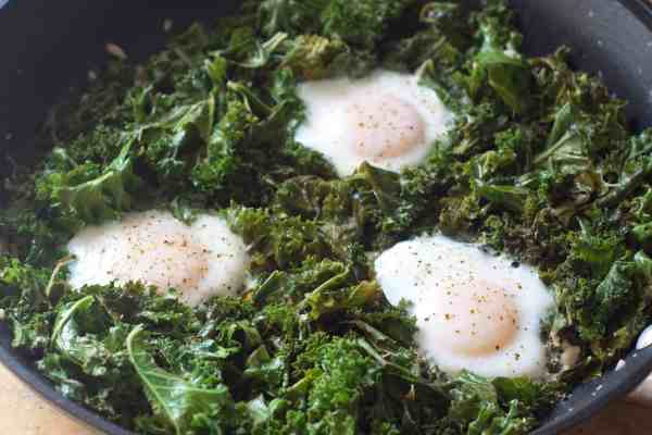 Simmered Eggs in chicken stock sautéed Kale. A hearty healthy way to start your day with plenty of greens!