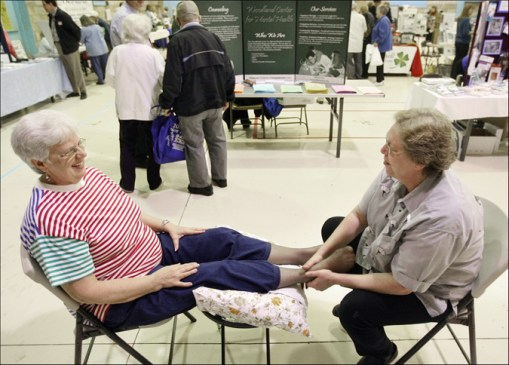 "Sharon LaPesh, left, of Hannibal, Mo., is all smiles while receiving a foot massage from massage therapist Kimberly Kircher during the 2009 Senior Expo Thursday at the Admiral Coontz Armory in Hannibal. Numerous vendors manned booths at the event to promote their services for area senior citizens. For LaPesh, massage was a highlight of the expo. ""Boy, that felt good,"" she said after Kircher completed her work. ""That's like a little piece of heaven."" H-W Photo/Philip Carlson"