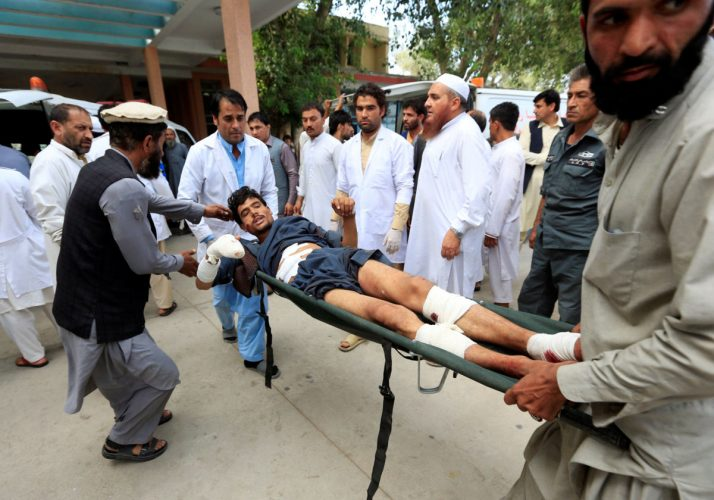 Afghan men carry an injured man to a hospital after a suicide attack, in Jalalabad, Afghanistan