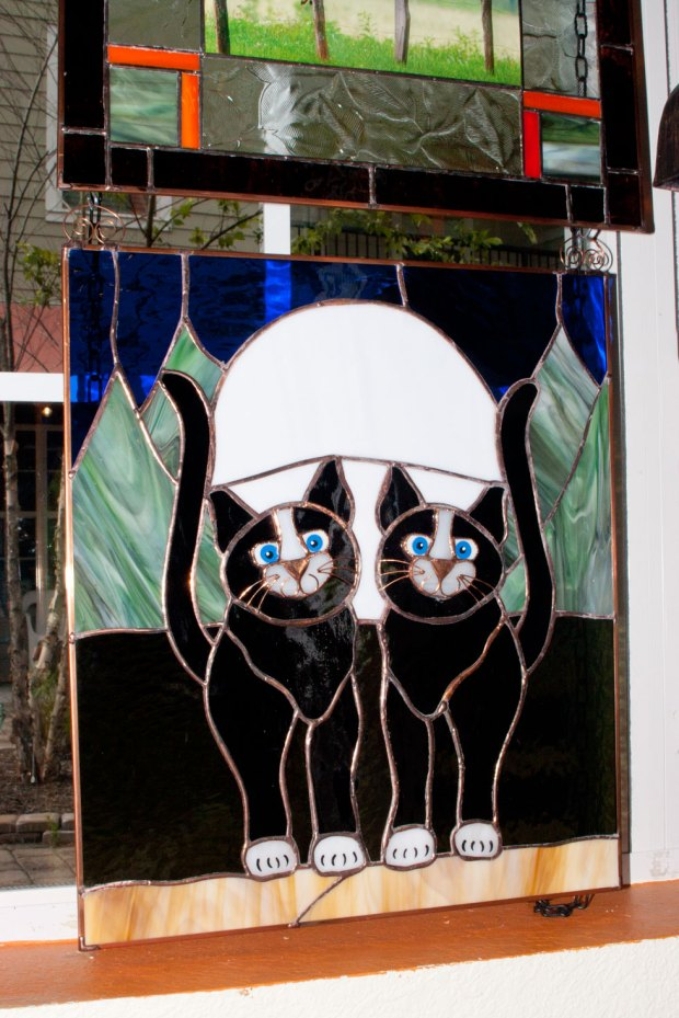 A cat-themed stained glass piece available in the Kat Kingdom gift shop.