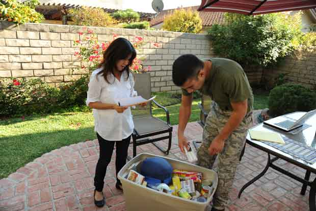 A military couple load their emergency kit on their patio during National Preparedness Month.