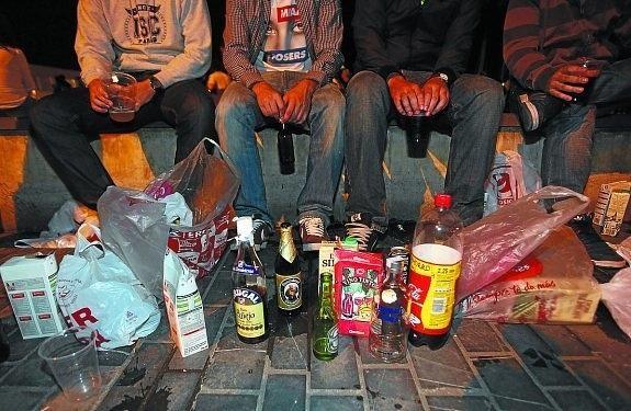 Jóvenes consumiendo alcohol en la calle.