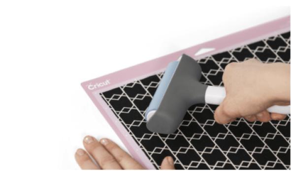 hand holding brayer pressing fabric onto pink cricut mat