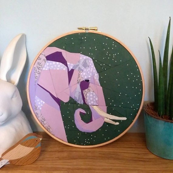 pictured finished elephant quilt block in an embroidery hoop