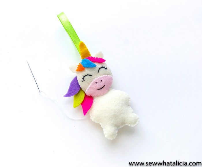 Christmas Unicorn Ornaments: This felt unicorn is seriously adorable. Hand sew this sweet little unicorn to use as an ornament or to adorn a gift. Click through for the full tutorial and printable pattern pieces. | www.sewwhatalicia.com