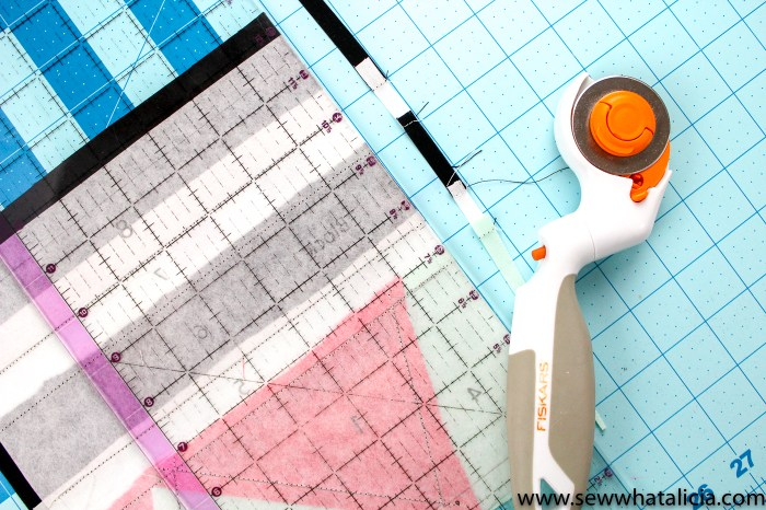 pictured: rotary cutter and ruler cutting the excess fabric from the edge of the block.