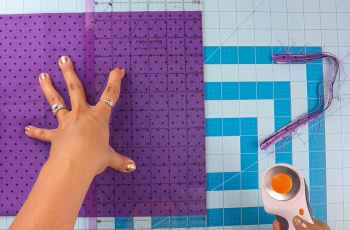 pictured: cutting mat with fabric and ruler, fabric has just been cut with rotary cutter