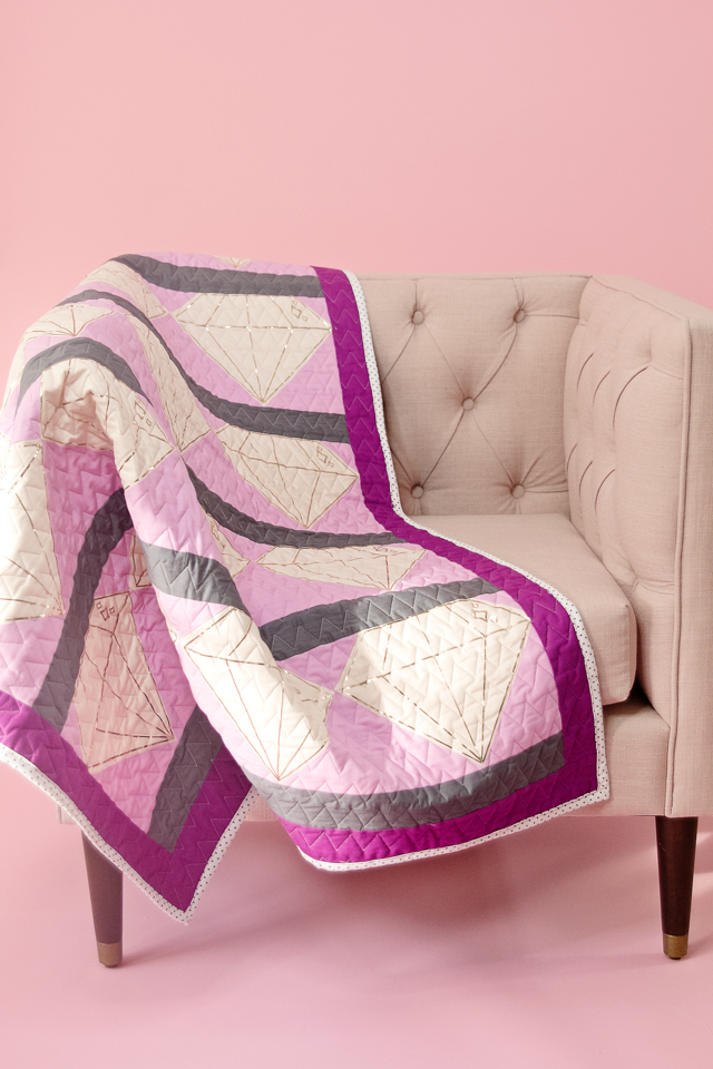 pictured purple, white, and grey gem quilt draped over chair