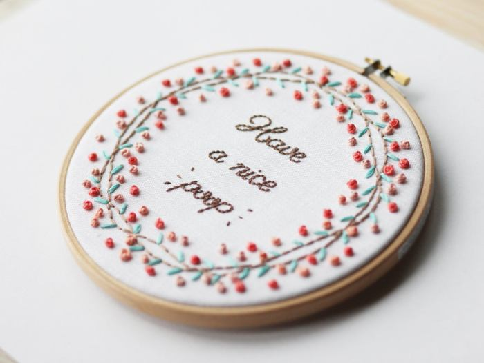 pictured embroidery hoop with have a nice poop text and floral wreath accent