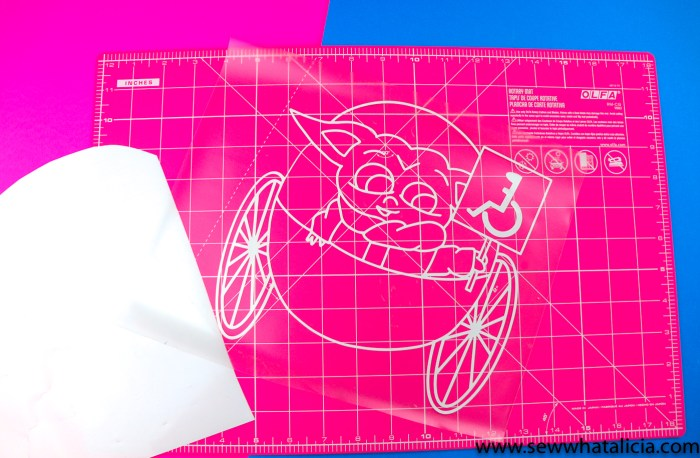 pictured baby yoda in white vinyl on a pink cutting mat