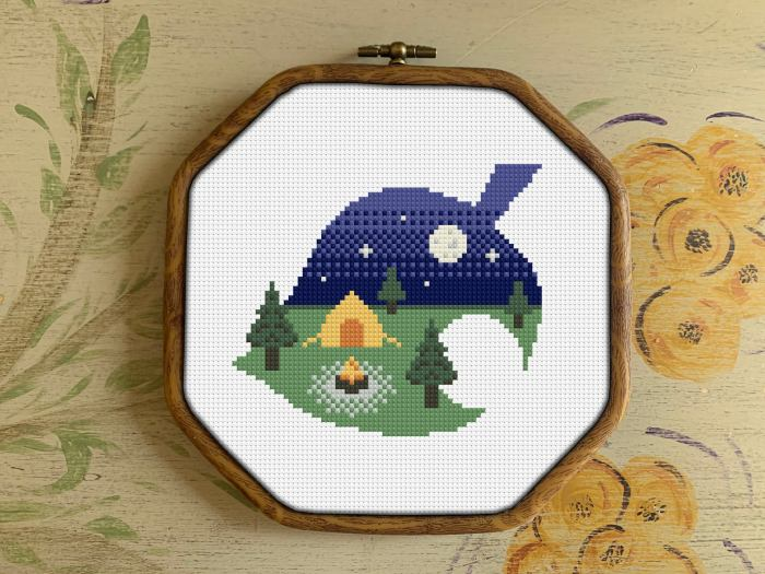 pictured cross stitch campsite pattern on white fabric with floral backdrop