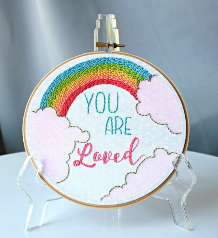 pictured rainbow in embroidery floss with the words you are loved embroidered