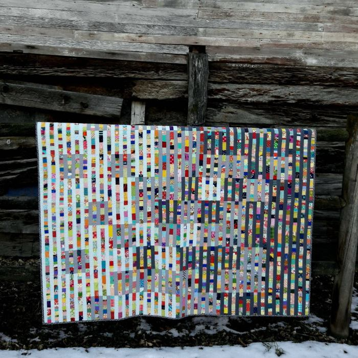 quilt on a wooden backdrop with snow on the ground
