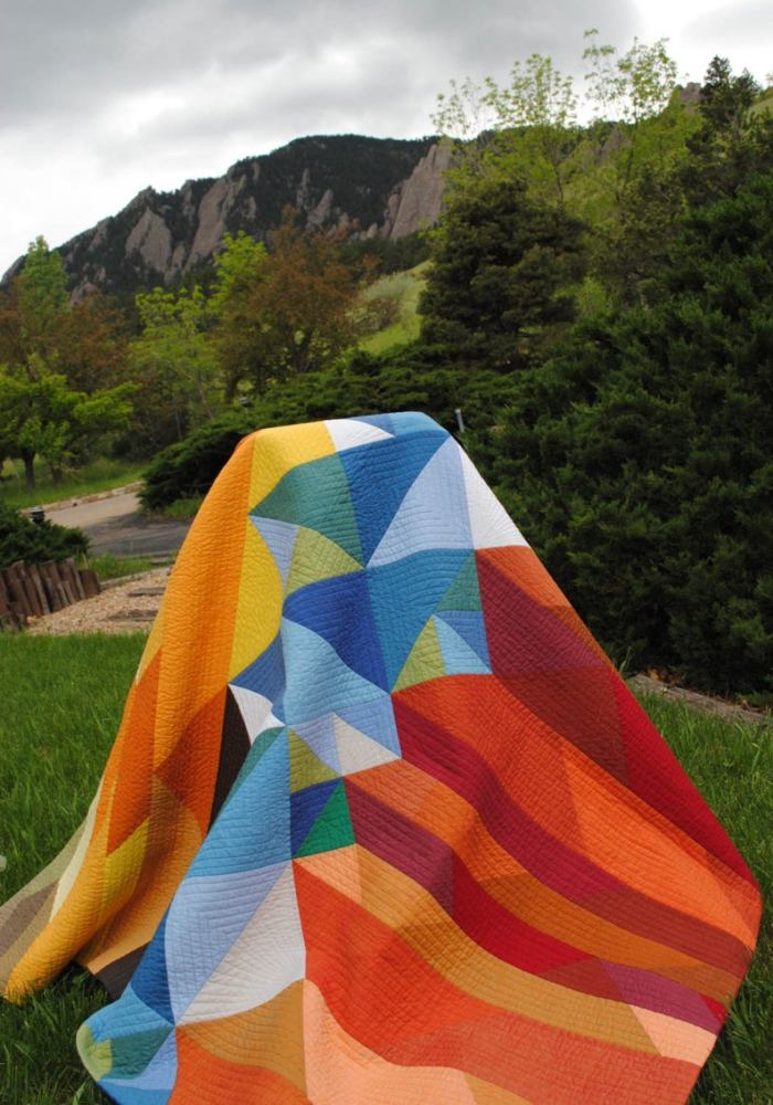 colorful colorado modern quilt hanging over a chair with bluffs in the background
