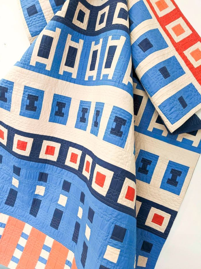 pictured blue, cream, and orange quilt with various sized squares